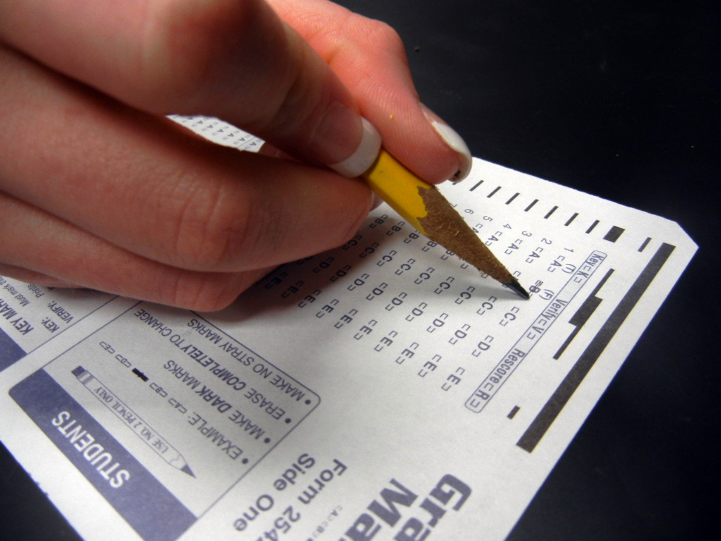 A close up of a student's hand marking a standardized test with a pencil