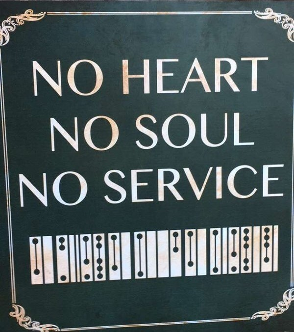 """A sign reading """"NO HEART NO SOUL NO SERVICE"""" in English and Clickwise"""